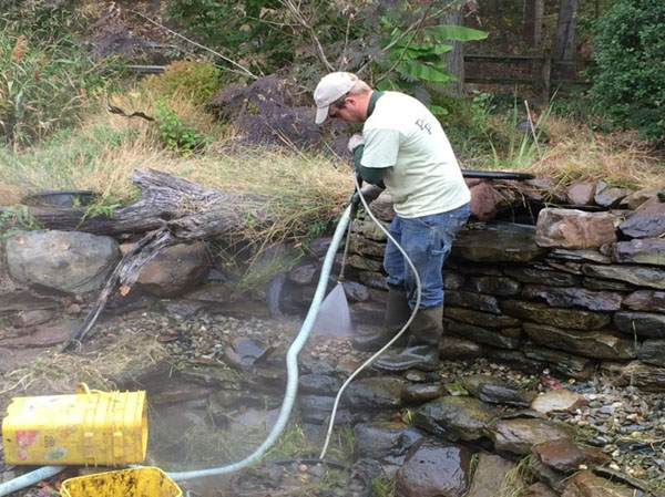 Pressure washing the pond shelves and walls during spring pond cleaning